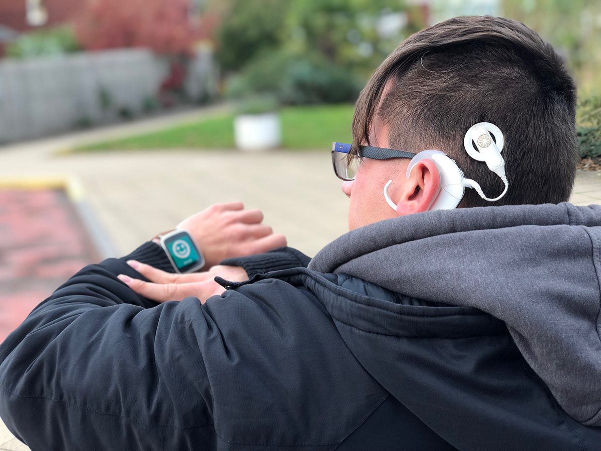 User with hearing aid showing the 'you have arrived' icon on their watch